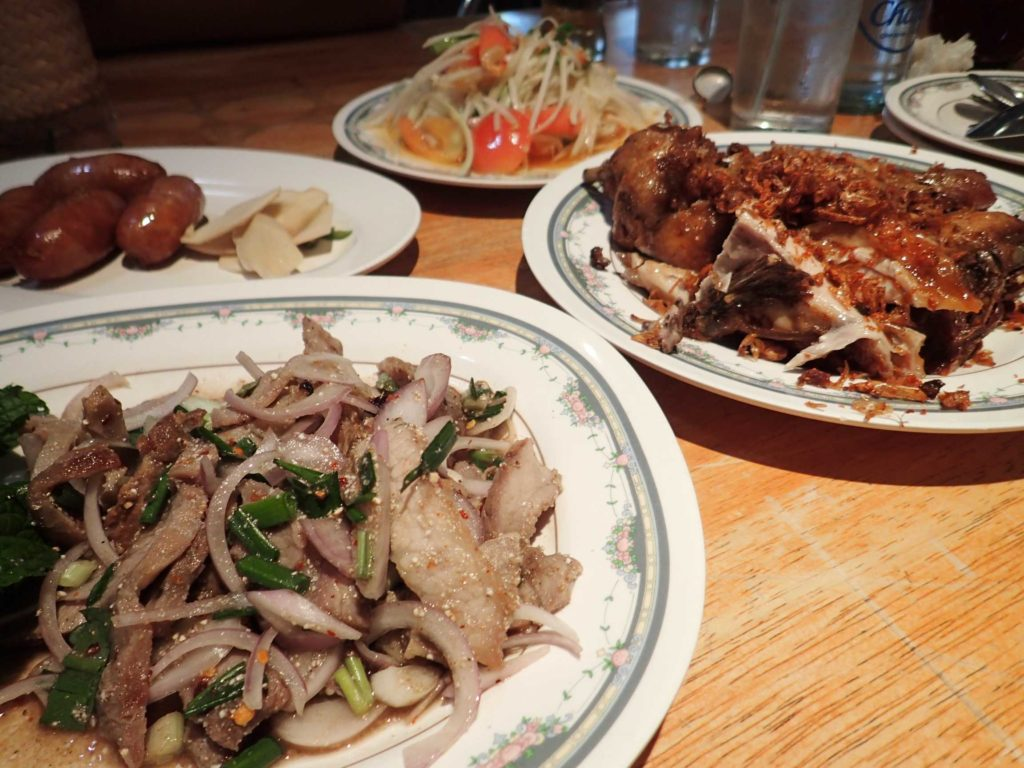 Nam tok moo (literally 'pork waterfall') in the foreground, garlic pork sausages, som tam (spicy papaya salad), and the famous Polo Fried Chicken