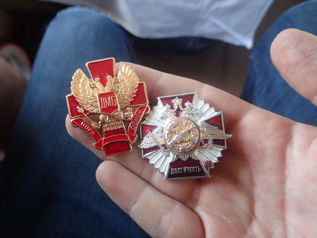 Military badges. He later gave the one on the right to me, using Google Translate to say 'souvenir' - I was humbled and surprised... I hope he can get another