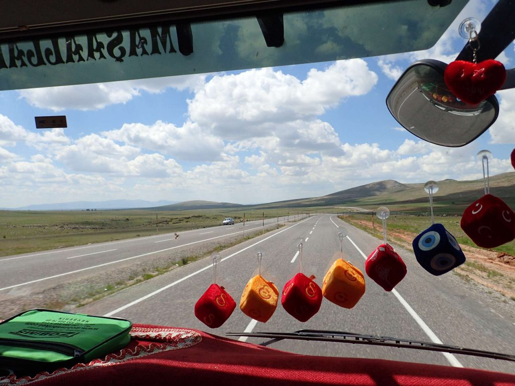 The interior of Gökhan's truck. He had a large gearstick which would click and whirr as he lazily accelerated and decelerated. He could often be found with a foot on the steering wheel, his seat, or even out the window. Cruise control was used liberally.