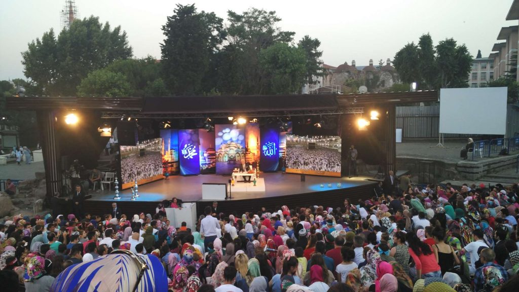 A man who seemed to be doing an iftar (sundown feast) television broadcast had attracted a large audience. He would occasionally take questions from the crowd.