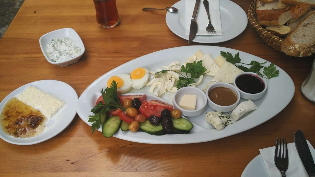 Turkish breakfast, featuring a variety of cheeses, olives, spreads, and the crowd favourite, bal kaymak on the left